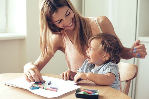 Smiling woman and toddler boy sitting at a table coloring.